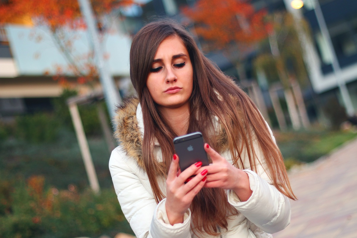 Millenial Woman holding phone in her hand