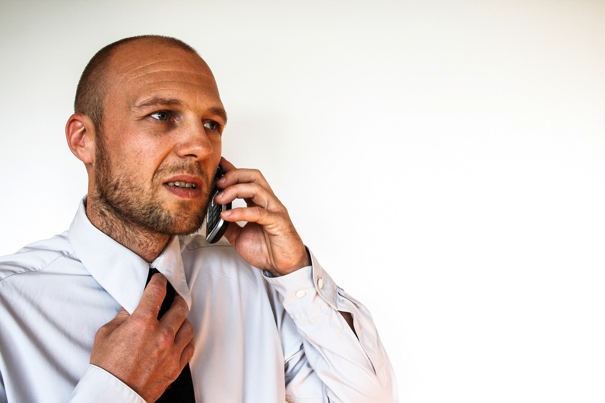 Man talking for the phone and loosing his tie
