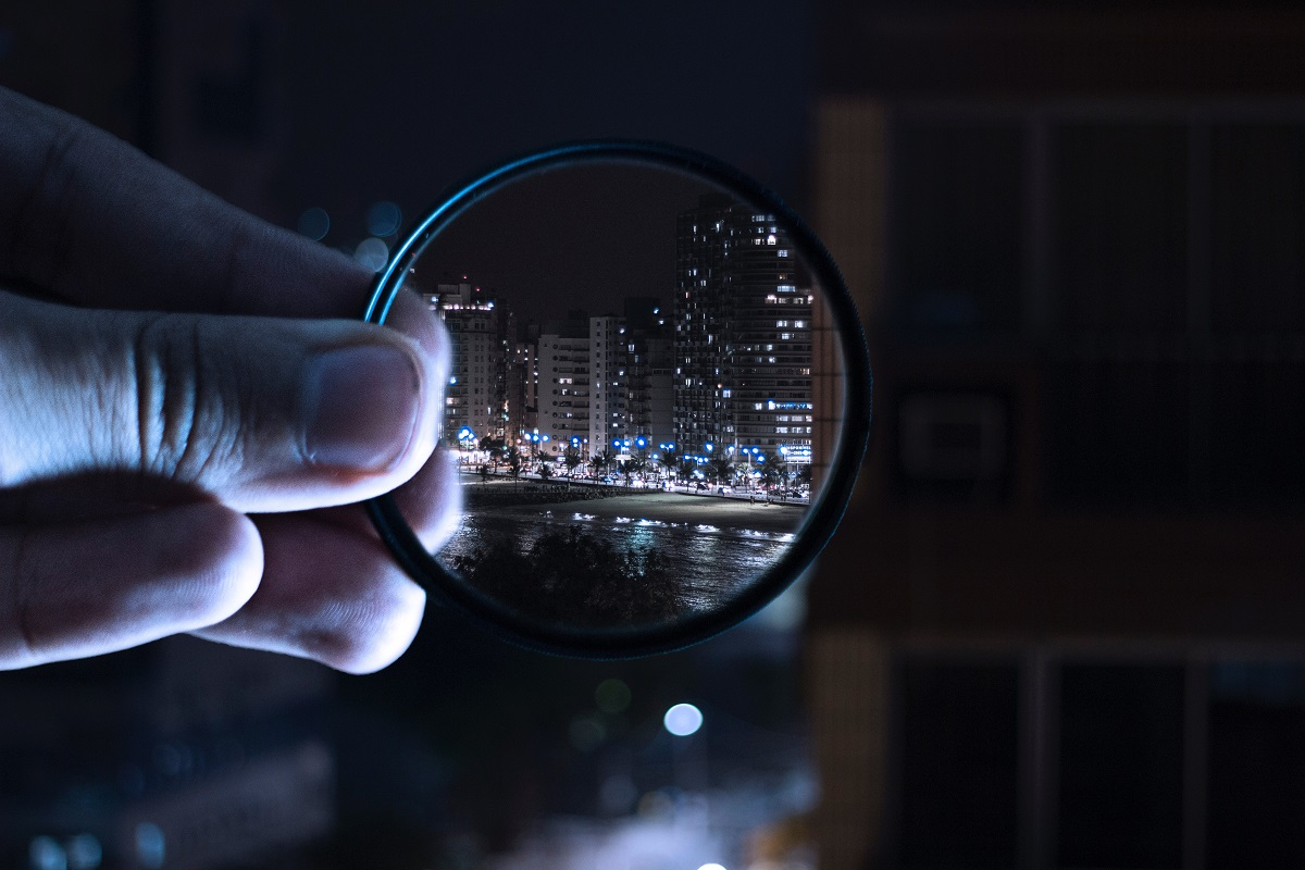 man holding the magnifying glass in hand to focus on a building
