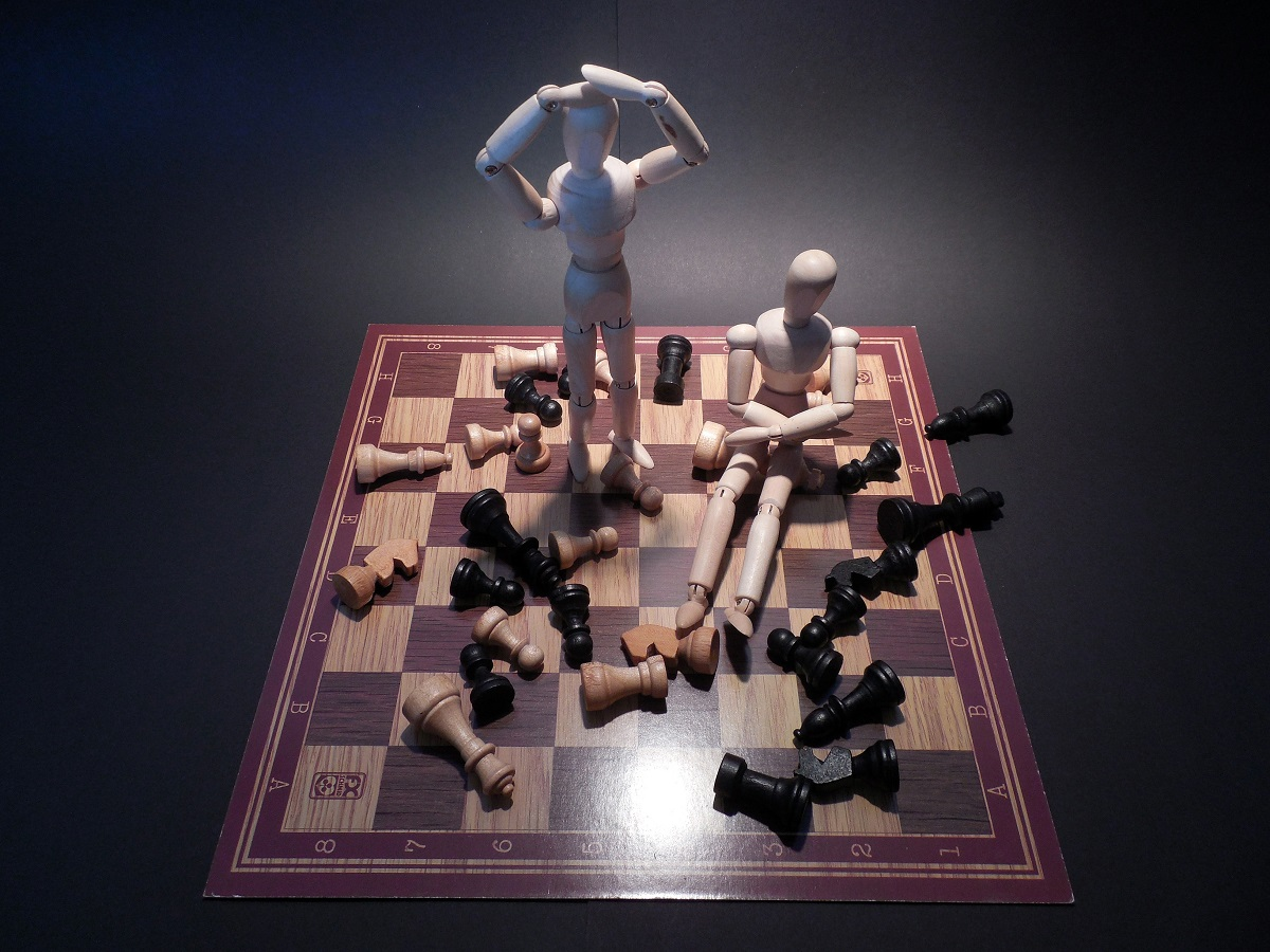 2 frustrated men ignoring what's going around has been symbolized with chessmen on the board
