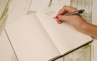 lady's hand jotting down her upcoming plan on the diary